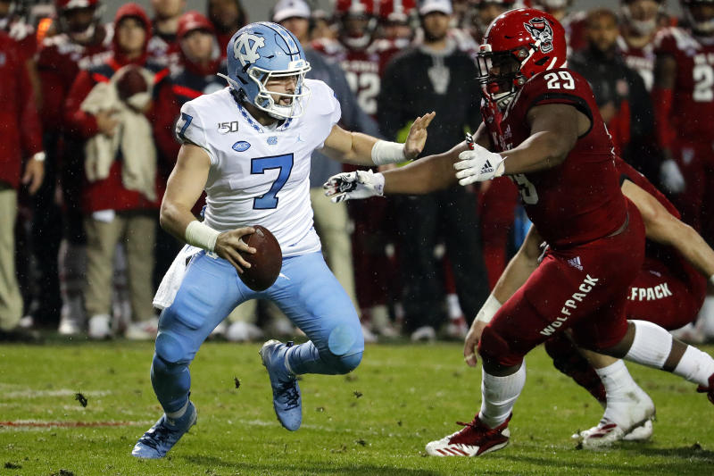 North Carolina quarterback Sam Howell (7) tries to avoid the rush of North Carolina State's Alim McNeill (29) during the first half of an NCAA college football game in Raleigh, N.C., Saturday, Nov. 30, 2019. (AP Photo/Karl B DeBlaker)
