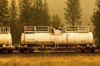 Firefighters ride atop a fire train while battling the Dixie Fire in Plumas County, Calif., on Saturday, July 24, 2021. The train is capable of spraying retardant to coat tracks and surrounding land. (AP Photo/Noah Berger)