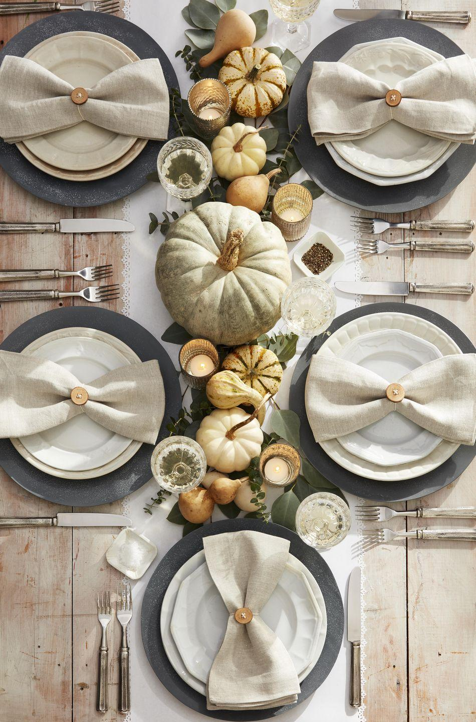<p>Neutral tones, including whitewashed pumpkins and dried gourds, are layered on top of a smattering of green eucalyptus leaves to create this sophisticated, neutral-toned centerpiece. Bonus: Thread twine through wood buttons and use to tie up linen napkins. <br></p>