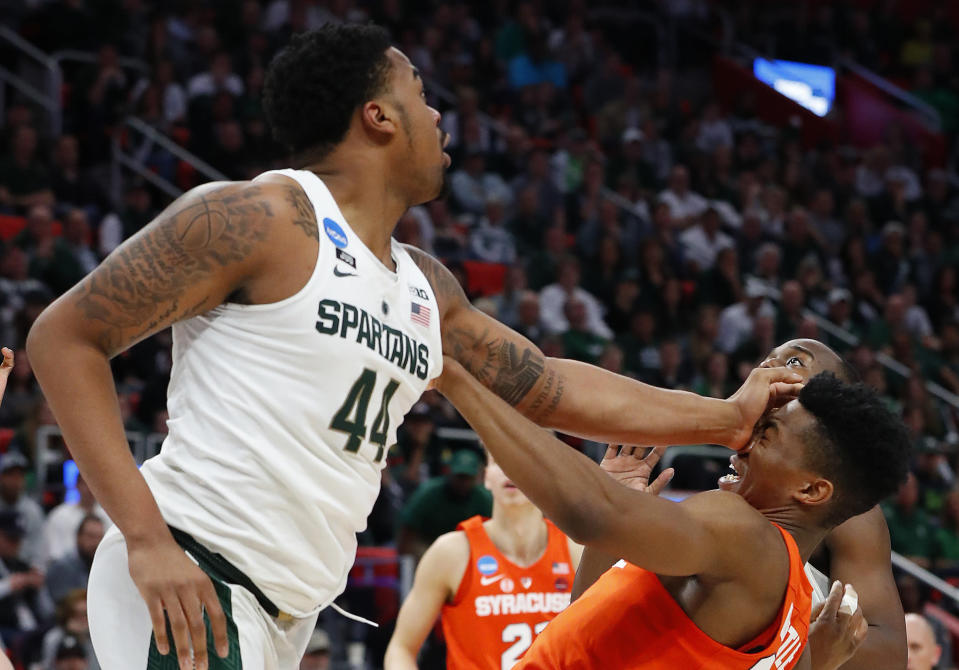 Michigan State forward Nick Ward (44) puts a hand to the face of Syracuse guard Tyus Battle (25) during the second half of an NCAA men's college basketball tournament second-round game in Detroit, Sunday, March 18, 2018. (AP Photo/Paul Sancya)