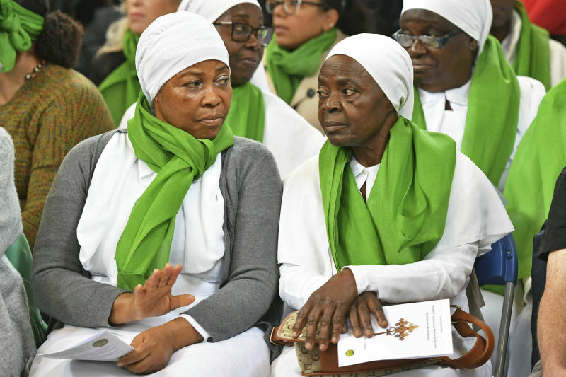 Members of the congregation wearing green as a symbol of remembrance, during a service of remembrance at St Helen's church to mark the two-year anniversary of the Grenfell Tower apartment block fire, near to the site of the fire in London, Friday June 14, 2019.  Two years after the 24-storey tower-block fire that killed 72 people, campaigners say hundreds of apartment buildings remain at risk of a similar blaze. (Dominic Lipinski/PA via AP)