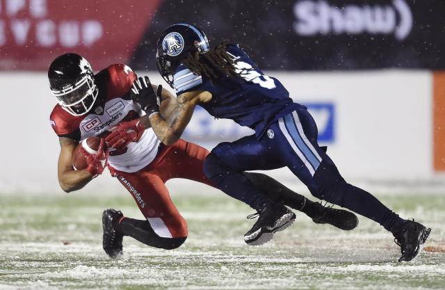 Calgary Stampeders wide receiver Juwan Brescacin is tackled by Toronto Argonauts linebacker Marcus Ball during the second half of a CFL football game in the Grey Cup in Ottawa on Sunday, Nov. 26, 2017. (Nathan Denette/The Canadian Press via AP)