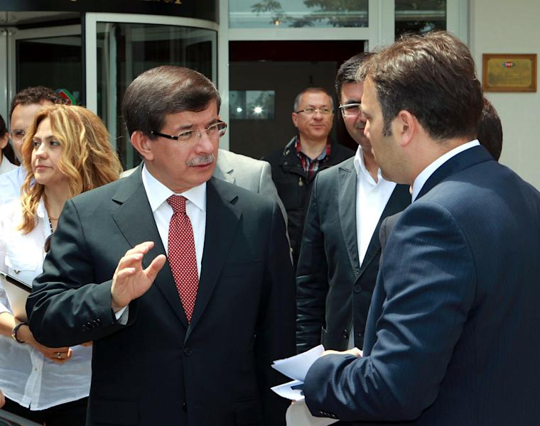 """In this image made available by the Turkish Foreign Ministry, Turkish Foreign Minister Ahmet Davutoglu, left, is seen talking to an advisor after an interview with the state-run TRT Television in Ankara, Turkey, Sunday, June 24, 2012. Davutoglu told State TV that Turkey would seek the meeting over article 4 of the NATO charter concerning Friday's incident. The article says member countries """"will consult together whenever, in the opinion of any of them, the territorial integrity, political independence or security of any of the parties is threatened."""" Davutoglu said Sunday that the jet was downed in international airspace after it mistakenly entered Syria, but the plane was not on a spying mission.(AP Photo/Hakan Goktepe, Turkish Foreign Ministry, HO)"""