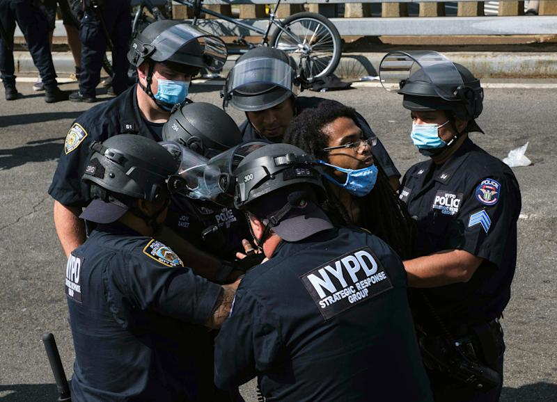 A Black Lives Matter protester is apprehended by NYPD officers on Brooklyn Bridge, Wednesday, July 15, 2020, in New York. Several New York City police officers were attacked and injured Wednesday on the Brooklyn Bridge during a protest sparked by the death of George Floyd. Police say at least four officers were hurt, including the department's chief, and more than a dozen people were arrested.