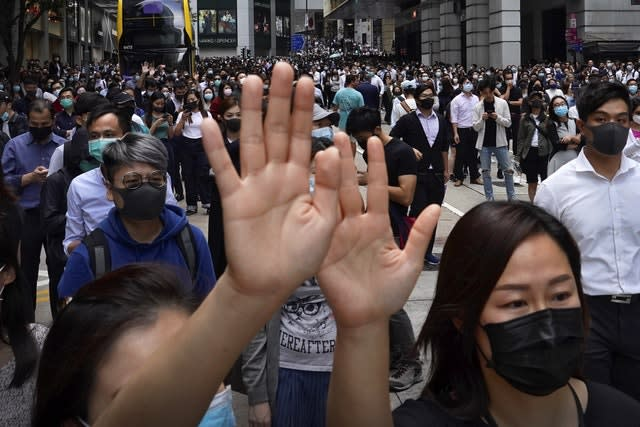 Office workers hold up their hands to represent their five demands