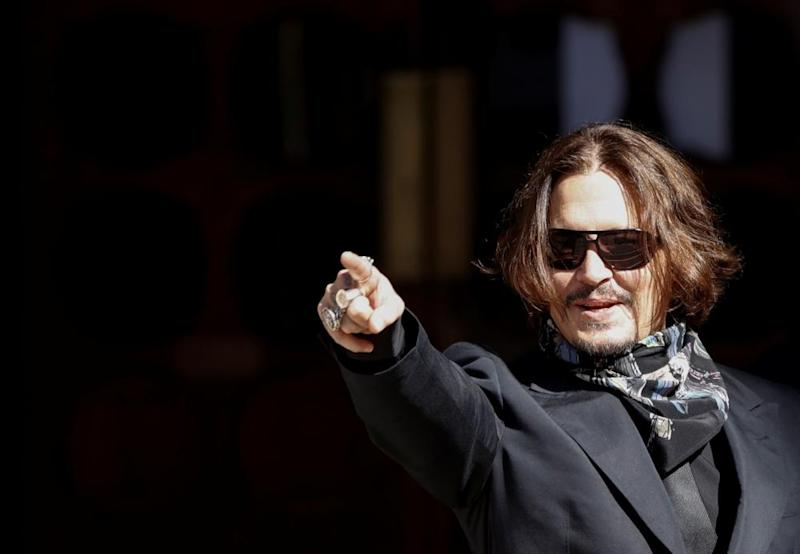 Johnny Depp gestures as he arrives at the High Court