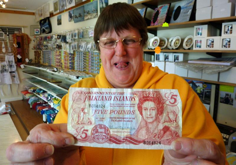In this photo taken on Sunday, March 4, 2012, Sybie Summers, owner of the Pod gift shop, shows a five pounds note of local currency in Stanley, Falkland Islands. Falkland Islanders are still bristling over the invasion by Argentina 30 years ago, but they're not complaining about its aftermath. The April 2, 1982 invasion led by Argentina's dictators and the subsequent war with Britain launched a process that transformed the islands from a sleepy backwater of sheep farms into a prosperous outpost whose residents enjoy one of the highest per capita incomes in the Western Hemisphere. (AP Photo/Michael Warren)