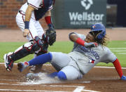 Toronto Blue Jays Vladimir Guerrero Jr. scores past Atlanta Braves catcher Travis D'Arnaud on a sacrifice fly by Danny Jansen during the second inning in a baseball game on Wednesday, Aug. 5, 2020, in Atlanta. (Curtis Compton/Atlanta Journal-Constitution via AP)