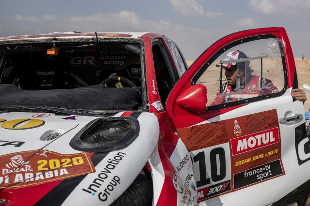 Driver Fernando Alonso, of Spain, walks into his Toyota at the end of stage ten of the Dakar Rally between Haradth and Shubaytah, Saudi Arabia, Wednesday, Jan. 15, 2020. (AP Photo/Bernat Armangue)