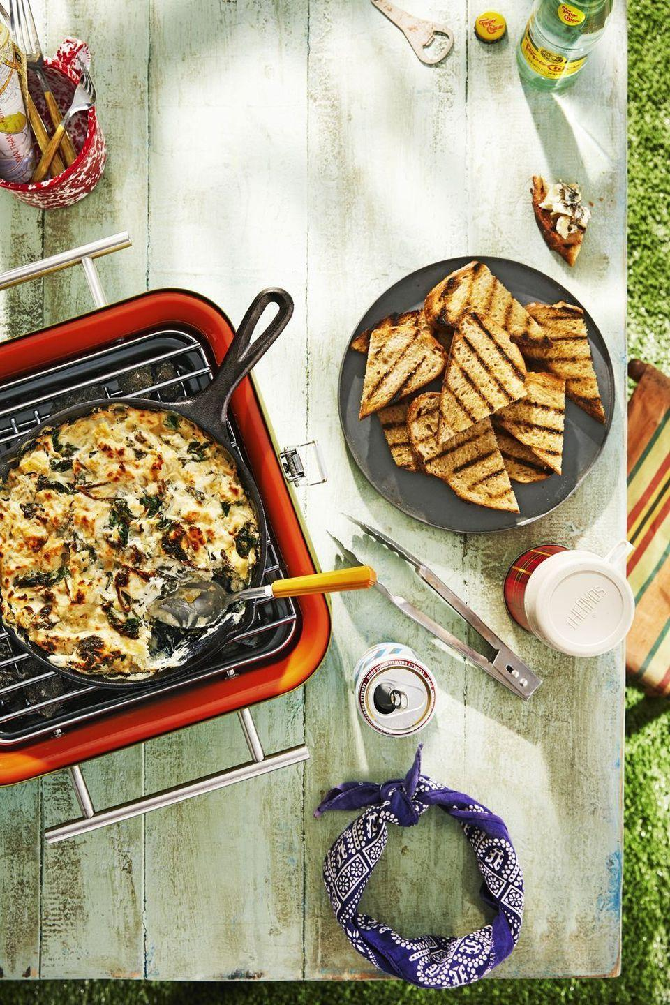 """<p>A classic app get a smoky treatment when cooked on a a grill. Serve with oil and grilled bread for dipping. <br></p><p><strong><a href=""""https://www.countryliving.com/food-drinks/a28071095/skillet-spinach-artichoke-dip-with-fire-roasted-bread-recipe/"""" rel=""""nofollow noopener"""" target=""""_blank"""" data-ylk=""""slk:Get the recipe"""" class=""""link rapid-noclick-resp"""">Get the recipe</a>.</strong><br> </p>"""