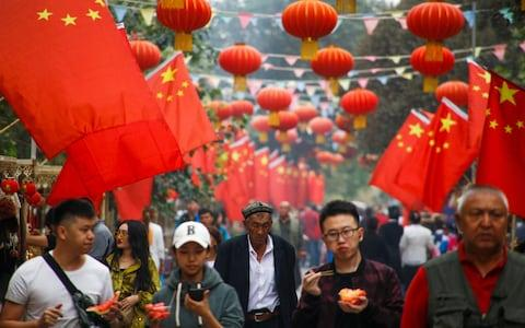 People walk under Chinese national flags in the Old City in Kashgar in Xinjiang - Credit: REUTERS/Thomas Peter