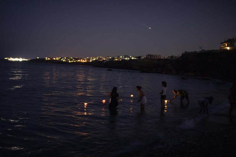 People place candles and flowers into the sea in Mati near Athens, on Tuesday, July 23, 2919, in the memory of the victims of a fire at a beach. A year ago Tuesday, a wildfire gutted the nearby resort of Mati and other seaside areas, destroying more than a thousand homes and killed over 100 people. (AP Photo/Petros Giannakouris)