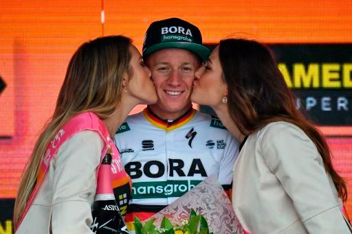 Germany's Pascal Ackermann receives the kiss of the race's hostesses on the podium after winning the fifth stage of the Giro D'Italia, tour of Italy cycling race, from Frascati to Terracina, Wednesday, May 15, 2019. Pascal Ackermann of Germany sprinted to victory at the end of the rain-affected fifth stage of the Giro d'Italia as Slovenian cyclist Primoz Roglic remained overall leader. (Alessandro Di Meo/ANSA via AP)