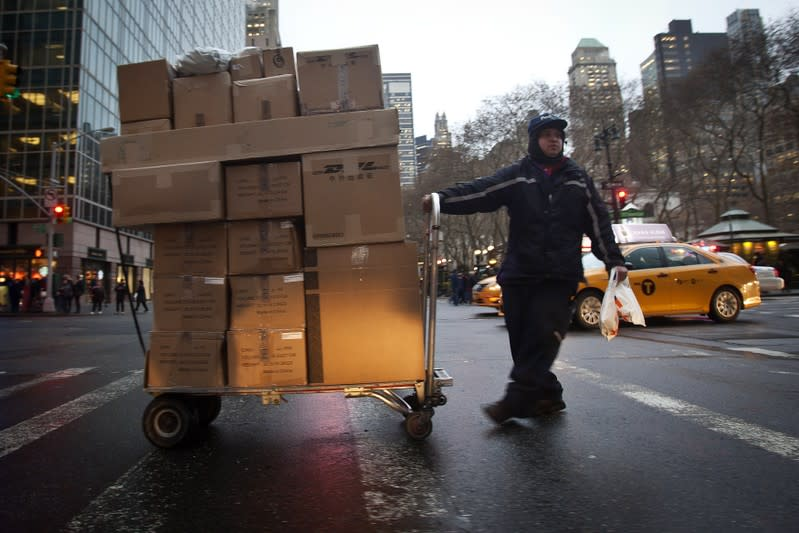 A FedEx delivery person wheels a trolley full of packages across 42nd Street in New York