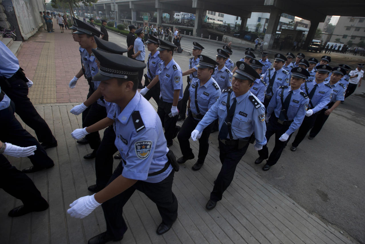 Chinese police officers march into the the Jinan Intermediate People's Court in Jinan to prepare for the arrival of former politician Bo Xilai in eastern China's Shandong province on Thursday, Aug. 22, 2013. Former Chinese politician Bo Xilai will stand trial at the court on Thursday on charges of corruption and abuse of power. (AP Photo/Ng Han Guan)