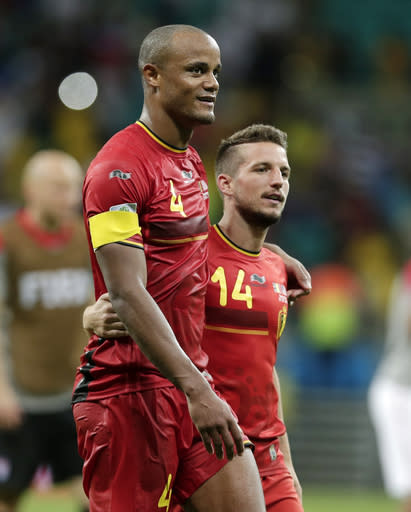 Belgium's Vincent Kompany (4) and Dries Mertens walk off the pitch after Belgium defeated the USA 2-1 in extra time to advance to the quarterfinals during the World Cup round of 16 soccer match between Belgium and the USA at the Arena Fonte Nova in Salvador, Brazil, Tuesday, July 1, 2014. (AP Photo/Marcio Jose Sanchez)