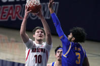 Arizona forward Azuolas Tubelis (10) drives on UCLA guard Johnny Juzang (3) during the first half of an NCAA college basketball game Saturday, Jan. 9, 2021, in Tucson, Ariz. (AP Photo/Rick Scuteri)