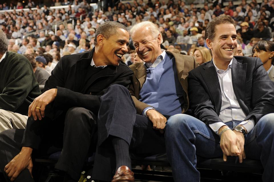 Barack Obama, then-Vice President Joe Biden and Hunter smile while seated in a crownd at a sports arena