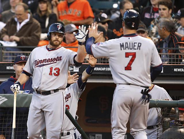 Minnesota Twins first baseman Joe Mauer (7) is congratulated by teammate Jason Kubel (13) after scoring a run against the San Francisco Giants in the third inning of a baseball game Friday, May 23, 2014, in San Francisco. (AP Photo/Tony Avelar)