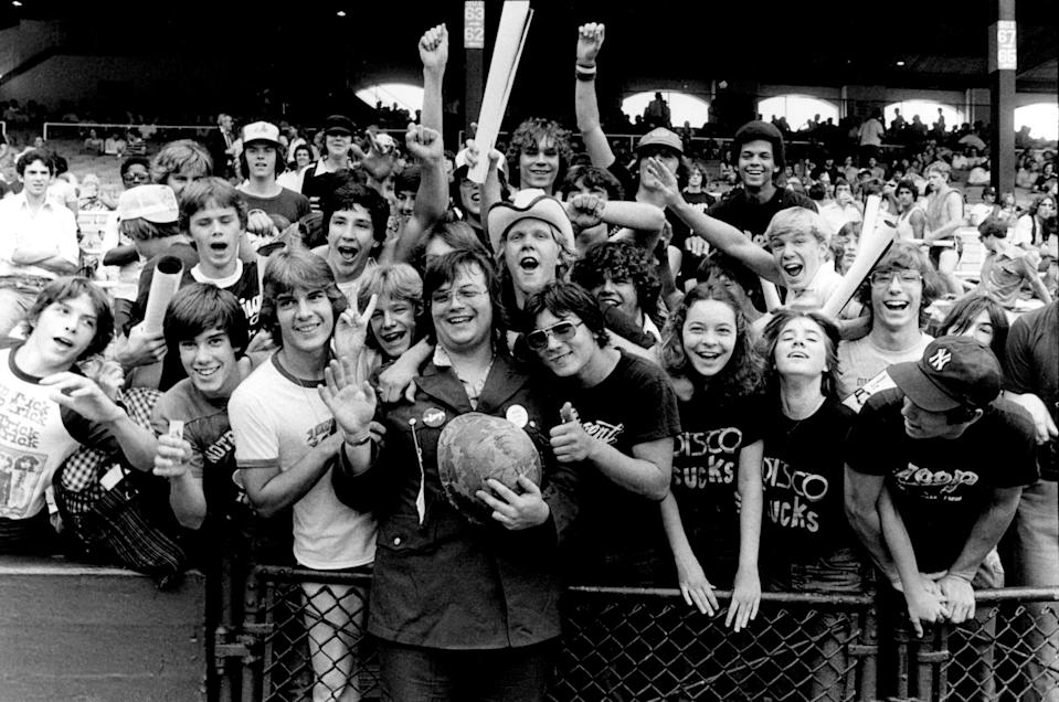 View of the crowd, some wearing 'Disco Sucks' and WLUP 'The Loop' t-shirts, surrounding Chicago DJ Steve Dahl, wearing military clothing and holding a helmet, during the anti-disco promotional event Disco Demolition Night, held in between games of a nighttime doubleheader between the Chicago White Sox and the Detroit Tigers, Chicago, Illinois, July 12, 1979. (Photo: Paul Natkin/Getty Images)