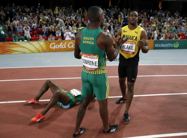 Athletics - Gold Coast 2018 Commonwealth Games - Men's 100m Final - Carrara Stadium - Gold Coast, Australia - April 9, 2018. Gold medalist Akani Simbine of South Africa, silver medalist Henricho Bruintjies of South Africa and bronze medalist Yohan Blake of Jamaica. REUTERS/Paul Childs