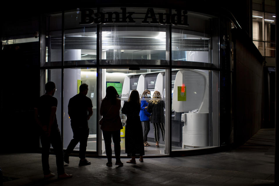 Clients wait to use ATM machines outside a closed bank in Beirut, Lebanon, Wednesday, June 2, 2021. In a reflection of the growing turmoil, scores of Lebanese depositors queued at ATM machines late Wednesday following a decision by the Central Bank that suspended an earlier decree allowing them to withdraw dollars stuck at the bank at a rate two and a half times better than the fixed exchange rate. (AP Photo/Hassan Ammar)