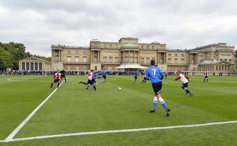 Polytechnic FC (in blue), during their match with the Civil Service FC in Buckingham Palace's garden, central London Monday Oct. 7, 2013. The Duke of Cambridge, president of the FA, helped organise the event, the first of its kind at Queen Elizabeth II's London home, as part of the Football Association's 150th anniversary celebrations. (AP Photo/ Toby Melville, Pool)