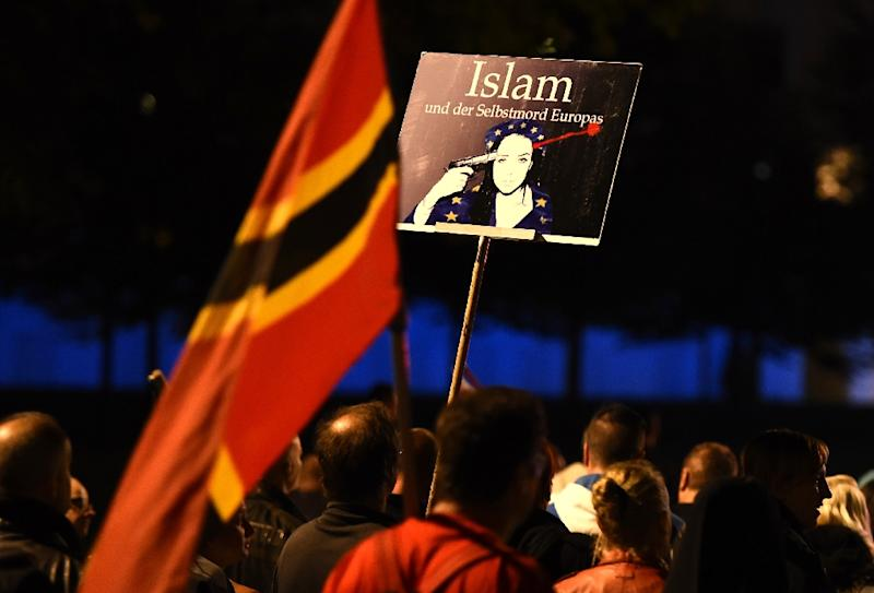A supporter of the PEGIDA movement holds a poster reading 'Islam and a European suicide' during a protest rally on October 5, 2015 in Dresden (AFP Photo/Tobias Schwarz)