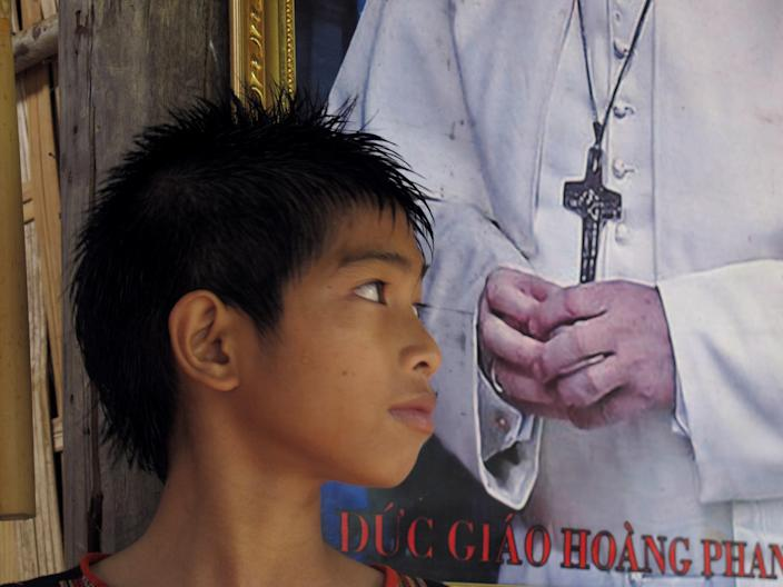 In this Thursday, Sept. 26, 2013 photo, a young Roman Catholic boy stands next to a photograph of Pope Francis at a church in Mang Yang in Vietnam's central highlands. Communist Vietnam allows state-sanctioned faiths to grow, but continues to keep a close watch on all religious institutions. (AP Photo/Chris Brummitt)