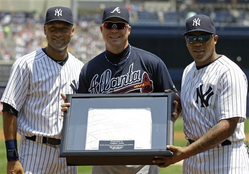 New York Yankees' Derek Jeter, left, and Andruw Jones, right, pose with Atlanta Braves Chipper Jones (10) after presenting Jones with a third base from Tuesday's night game before the two teams faced each other in a baseball game at Yankee Stadium in New York, Wednesday, June 20, 2012. Jones is retiring at the end of the season. (AP Photo/Kathy Willens)