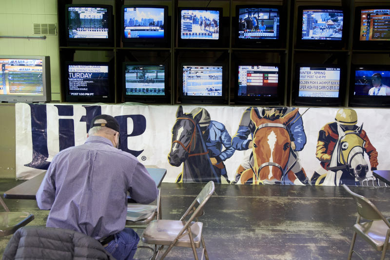 A person waits for the horses to race at Fonner Park in Grand Island, Neb., Saturday, March 14, 2020. Fonner was one of the few sporting venues in the country open to fans Saturday, unfortunately the races were called off due to dangerous track conditions following snowfall. (AP Photo/Nati Harnik)