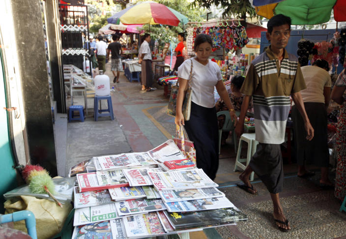 Pedestrians pass near a roadside newspaper shop in Yangon, Myanmar, Friday, Dec. 28, 2012. Myanmar said Friday it will allow private daily newspapers starting in April for the first time since 1964, in the latest step toward allowing freedom of expression in the long-repressed nation. (AP Photo/Khin Maung Win)