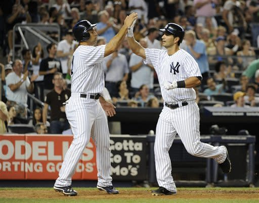 New York Yankees' Raul Ibanez, left, greets Eric Chavez after Chavez hit a two-run home run off Seattle Mariners starting pitcher Kevin Millwood, scoring Ibanez, in the sixth inning of a baseball gameFriday, Aug. 3, 2012, at Yankee Stadium in New York. (AP Photo/Kathy Kmonicek)