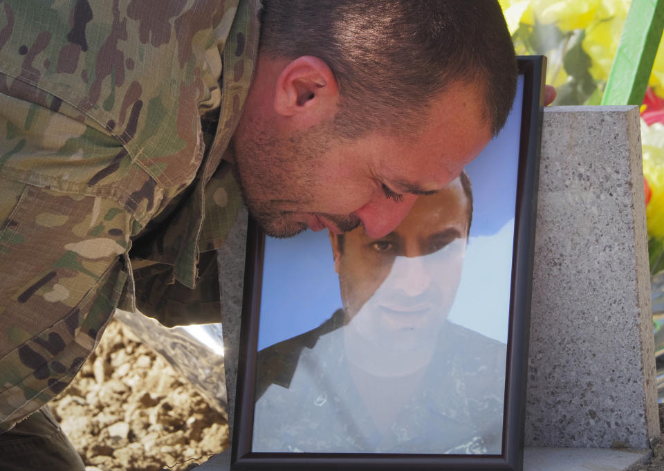 A man says goodbye during a funeral of his comrade at a cemetery in Stepanakert, the separatist region of Nagorno-Karabakh, Friday, Oct. 30, 2020. The Azerbaijani army has closed in on a key town in the separatist territory of Nagorno-Karabakh following more than a month of intense fighting. (AP Photo)