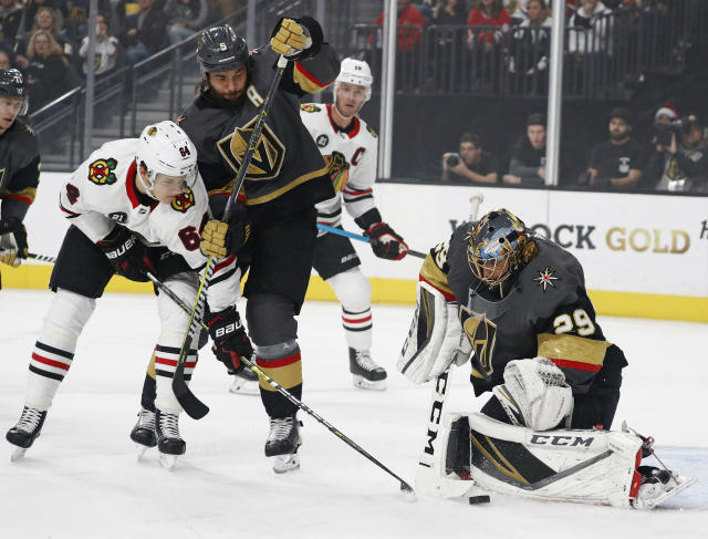 Vegas Golden Knights goaltender Marc-Andre Fleury (29) blocks a shot beside defenseman Deryk Engelland (5) and Chicago Blackhawks center David Kampf (64) during the first period of an NHL hockey game Thursday, Dec. 6, 2018, in Las Vegas. (AP Photo/John Locher)