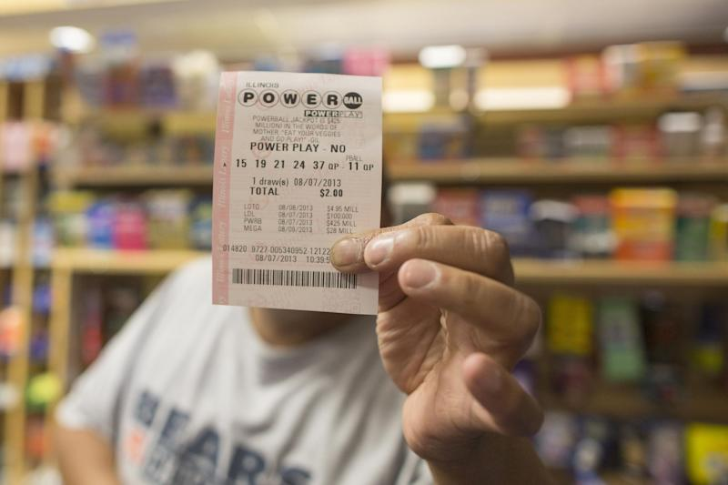 A man holds up his Powerball ticket inside of a convenience store in Chicago, Wednesday, Aug. 7, 2013. Ticketholders are hoping to win Wednesday's Powerball drawing, estimated at $425 million so far. (AP Photo/Scott Eisen)