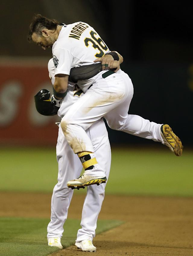 Oakland Athletics' Derek Norris (36) is hoisted up by Josh Donaldson after Norris made the game winning hit against the Tampa Bay Rays in the tenth inning of a baseball game Monday, Aug. 4, 2014, in Oakland, Calif. (AP Photo/Ben Margot)