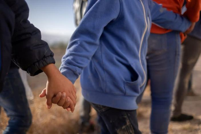Asylum seeking unaccompanied minors hold hands amid adult migrants from Central America as they await transport in Penitas, Texas