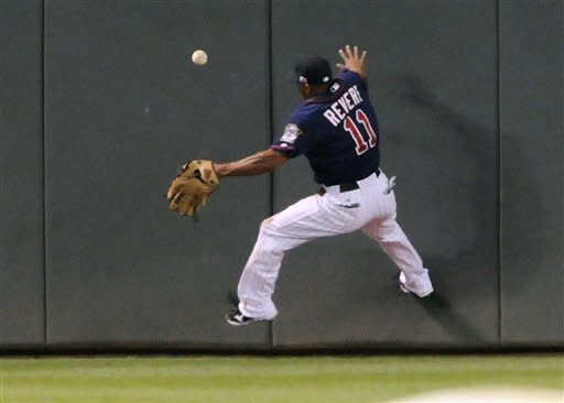 Minnesota Twins center fielder Ben Revere goes up the wall to chase a triple off the bat of Kansas City Royals' Alex Gordon in the third inning of a baseball game, Tuesday, Sept. 11, 2012, in Minneapolis. (AP Photo/Jim Mone)