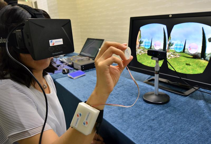 "A journalist tries to use ""3D-Haptics Technology"", at a press preview in Tsukuba, suburban Tokyo on September 1, 2014 (AFP Photo/Yoshikazu Tsuno)"