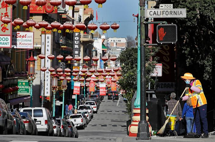 In this Jan. 31, 2020, file photo, a masked worker cleans a street in the Chinatown district in San Francisco. Police are stepping up patrol and volunteers are increasing their street presence after several violent attacks on older Asians stoked fear in the San Francisco Bay Area's Chinatowns and subdued the celebratory mood leading up to Chinese New Year.