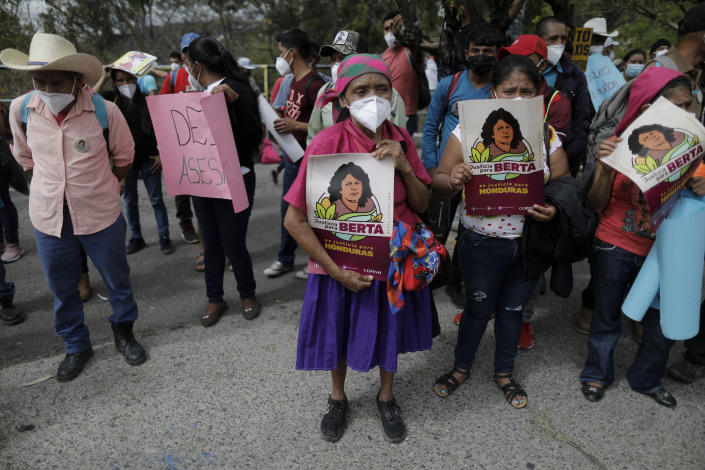 Activists and supporters of Honduran environmental and Indigenous rights activist Berta Caceres hold signs with her name and likeness during the trial against Roberto David Castillo, an alleged mastermind of her murder, outside of the Supreme Court building in Tegucigalpa, Honduras, Tuesday, April 6, 2021. The trial began five years after the prize-winning activist's murder. (AP Photo/ Elmer Martinez)