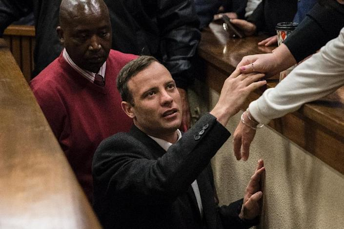 Oscar Pistorius holds the hand of a relative as he leaves the High Court in Pretoria, on July 6, 2016 after being sentenced to six years in jail (AFP Photo/Marco Longario)