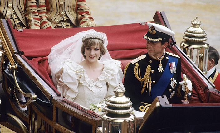 """Prince Charles, Prince of Wales and Diana, Princess of Wales, wearing a wedding dress designed by David and Elizabeth Emanuel and the Spencer family Tiara, ride in an open carriage, from St. Paul's Cathedral to Buckingham Palace, following their wedding on July 29, 1981 in London, England.<span class=""""copyright"""">Anwar Hussein—WireImage via Getty Images</span>"""
