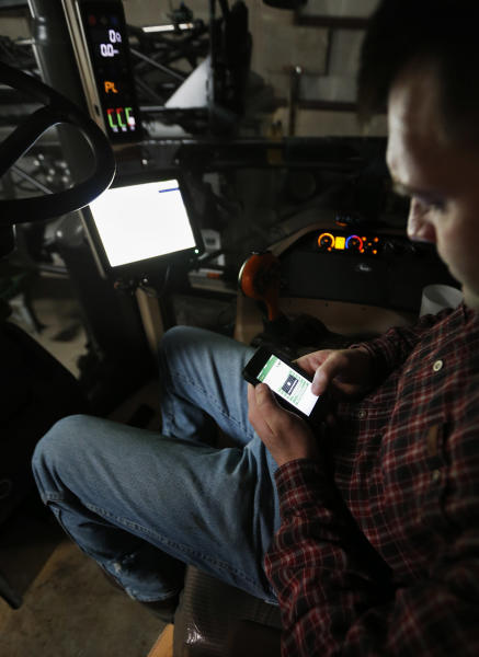 Nick Guetterman looks over the data shared by the crop sprayer he is seated in and cell phone while on his farm near Bucyrus, Kan., Wednesday, Feb. 19, 2014. Farmers from across the nation gathered in Washington this month for their annual trek to seek action on the most important matters in American agriculture. But this time, a new issue emerged: growing unease about how the largest seed companies are gathering vast amount of data from sensors on tractors, combines and other farm equipment. The sensors measure soil conditions, seeding rates, crop yields and many other variables. (AP Photo/Orlin Wagner)