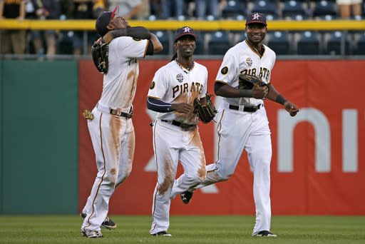 Pittsburgh Pirates left fielder Starling Marte, left, center fielder Andrew McCutchen, center, and right fielder Gregory Polanco run off the field after getting the final out of a 8-2 win over the Philadelphia Phillies in a baseball game in Pittsburgh, Friday, July 4, 2014. (AP Photo/Gene J. Puskar)