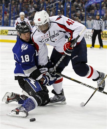 Tampa Bay Lightning's Adam Hall, left, and Washington Capitals' Joel Ward battle for the puck during the first period of an NHL hockey game, Saturday, Feb. 18, 2012, in Tampa, Fla. (AP Photo/Mike Carlson)