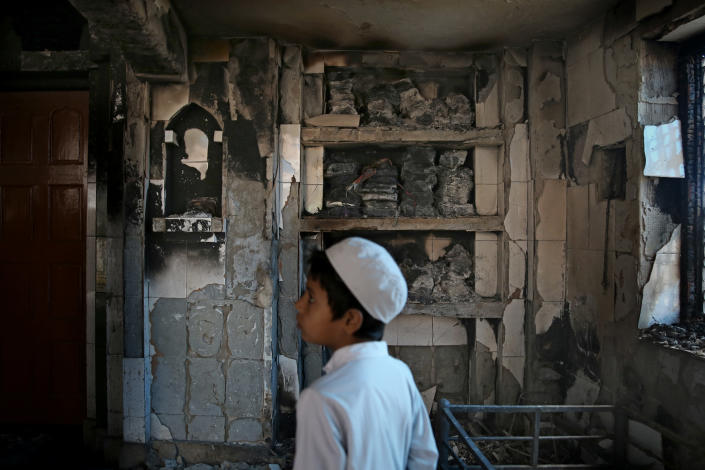 An Indian Muslim boy stands inside a mosque burnt in Tuesday's violence in New Delhi, India, Thursday, Feb. 27, 2020. India accused a U.S. government commission of politicizing communal violence in New Delhi that killed at least 30 people and injured more than 200 as President Donald Trump was visiting the country. The violent clashes between Hindu and Muslim mobs were the capital's worst communal riots in decades and saw shops, Muslim shrines and public vehicles go up in flames. (AP Photo/Altaf Qadri)