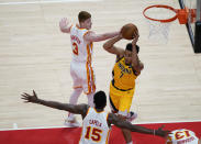 Indiana Pacers Malcolm Brogdon, center, passes the ball against the Atlanta Hawks defense during the first half of an NBA basketball game on Sunday, April 18, 2021, in Atlanta. (AP Photo/Brynn Anderson)
