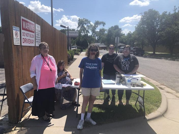 Antiabortion protesters stand near a table